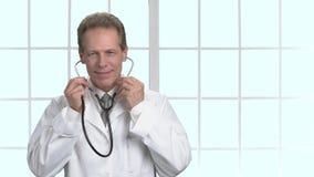 Maturi medico maschio della medicina che si prepara per esaminare il paziente ed aiutare video d archivio