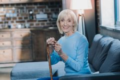 Cheerful woman holding a stick. Maturity. Gleeful grey-haired woman smiling while sitting on the sofa with her stick stock photos