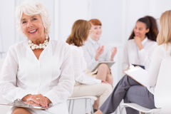 Maturity in women work office. Senior women sitting on a chair with other women employees at the background stock images