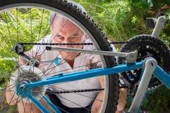 Maturo riparando una bicicletta Fotografia Stock
