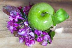 Maturo verde di melo di cremisi e della mela fiorisce su fondo di legno, pianamente disposizione Fotografie Stock