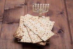 Matza judío con el menorah en la tabla Foto de archivo