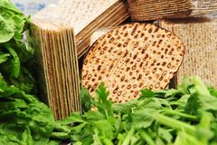 Matza for Passover. A variety of different types of matza (unleavened bread) surrounded by green leafy vegetables such as lettuce and celery - traditional food Stock Images