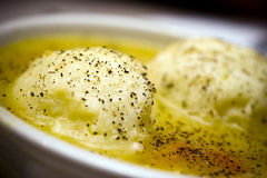 Matzah Ball Soup. Bowel of matzah ball soup with pepper.  Close-up/macro photograph Royalty Free Stock Images