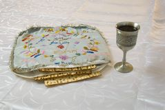 Matzah cover and wine. Matzo inside an antique embroidered matzo cover for the passover seder, next to a kiddush cup of wine Royalty Free Stock Image