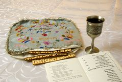 Matzah cover, wine and haggadah. Matzo in an antique embroidered matzo cover with kiddush cup of wine and traditional passover haggadah text Stock Images
