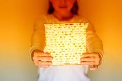 Matzah judío de la tenencia de la muchacha para la pascua judía fotografía de archivo