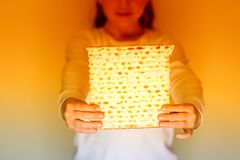 Matzah judaico da terra arrendada da menina para a páscoa judaica fotografia de stock