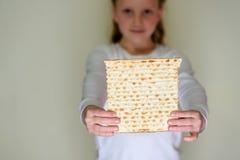 Matzah judaico da terra arrendada da menina para a páscoa judaica imagem de stock
