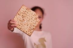 Matzah o matza de la tenencia de la chica joven Tarjeta jud?a de la invitaci?n o de felicitaci?n de la pascua jud?a de los d?as d imagenes de archivo