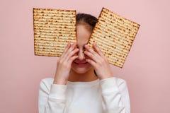 Matzah o matza de la tenencia de la chica joven Tarjeta jud?a de la invitaci?n o de felicitaci?n de la pascua jud?a de los d?as d fotos de archivo