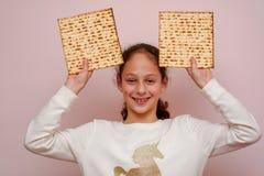 Matzah o matza de la tenencia de la chica joven Tarjeta jud?a de la invitaci?n o de felicitaci?n de la pascua jud?a de los d?as d fotografía de archivo libre de regalías
