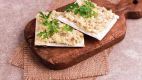 Matzo with kosher Forshmak on old wooden cutting board. With burlap napkin. Gray marble background stock video footage