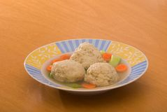 Matzoh Ball Soup. Chicken soup with matzoh balls; photographed on birch table Royalty Free Stock Photos