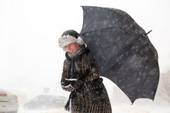 Menina com o guarda-chuva durante a tempestade da neve Imagens de Stock