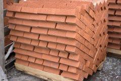 Mauerziegel des roten Lehms gestapelt auf den Paletten noch eingewickelt in ihrem Plastik für Lieferung an einem Lager-, Fabrik-  Stockfotografie