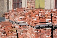 Mauerziegel des roten Lehms gestapelt auf Paletten für Lieferung Stockbild
