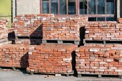 Mauerziegel des roten Lehms gestapelt auf Paletten für Lieferung Stockfotografie