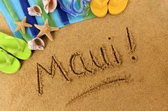 Maui Hawaii beach sand word writing. The word Maui written on a sandy beach, with scuba mask, beach towel, starfish and flip flops Royalty Free Stock Image