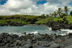 Maui Black Sand Beach. The black sand beach in Waianapanapa State Park in the small town Hana on the island of Maui in Hawaii Royalty Free Stock Photo