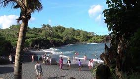 Maui, Hawaii - circa 2013: Tourists visit the Waianapanapa black sand beach. Waianapanapa Beach, Hawaii - circa 2013: Tourists visit the black sand beach at stock video