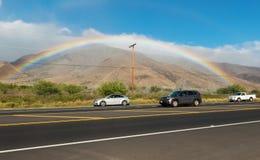 MAUI HAWAII, USA-18, 2014: regnbåge bredvid en huvudväg Arkivbild