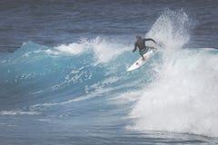 MAUI, HI - 10. MÄRZ 2015: Berufssurfer reitet ein riesiges wav Lizenzfreie Stockbilder