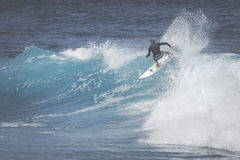 MAUI, HI - MARCH 10, 2015: Professional surfer rides a giant wav Royalty Free Stock Images