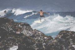 MAUI HI - MARS 10, 2015: Den yrkesmässiga surfaren rider en jätte- wav Arkivfoto