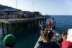 MAUMERE/INDONESIA-APRIL 26 2014年:小船准备在许多孩子等待他们的到来的船坞靠码头 免版税库存图片