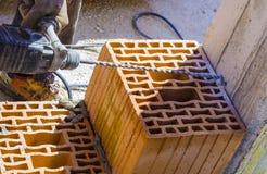 Maurer bohrt ein Loch mit einer Bohrmaschine stockfotografie