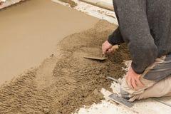 Maurer, der den Zementestrich planiert Stockbilder