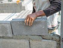 Maurer, der eine andere Reihe der Ziegelsteine in der Site niederlegt Lizenzfreies Stockfoto