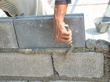 Maurer, der eine andere Reihe der Ziegelsteine in der Site niederlegt Lizenzfreie Stockfotografie