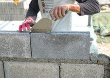 Maurer, der eine andere Reihe der Ziegelsteine in der Site niederlegt Stockbild