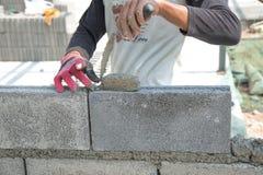 Maurer, der eine andere Reihe der Ziegelsteine in der Site niederlegt Stockbilder
