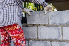 Maurer, der eine andere Reihe der Ziegelsteine in der Site niederlegt Lizenzfreie Stockbilder