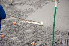 Maurer, der eine erste Schicht des Frischbetonbodens an der Hausgrundlage aufbaut und planiert lizenzfreies stockbild