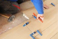 Maurer, der einen Porzellanfliesenboden in Nachahmung des Buchenholzes legt Lizenzfreie Stockbilder