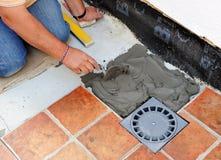 Maurer, der neuen Abfluss im Boden der Terrasse eines Hauses legt Stockfotografie