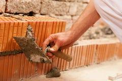 Maurer, der Wand mit Ziegelstein und Bewurf herstellt stockfotos
