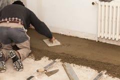 Maurer machen den Zementestrich glatt Stockbild