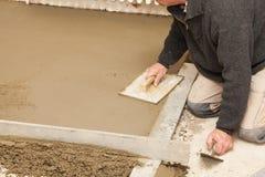 Maurer machen den Zementestrich glatt Lizenzfreies Stockbild
