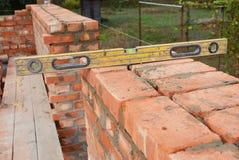 Maurerarbeit mit dem Geist-Niveau, zum der neuen Hausmauer des roten Backsteins zu überprüfen Lizenzfreie Stockfotos