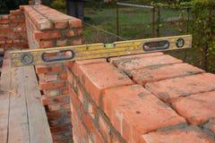 Maurerarbeit mit dem Geist-Niveau, zum der neuen Hausmauer des roten Backsteins zu überprüfen im Freien Grundlegende Maurerarbeit Lizenzfreie Stockbilder
