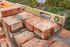 Maurerarbeit mit dem Geist-Niveau, zum der neuen Hausmauer des roten Backsteins zu überprüfen im Freien Grundlegende Maurerarbeit Stockfotos