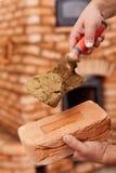 Maurerarbeitheizungs-Erbauerhand mit Ziegelstein und Trowel Stockbild