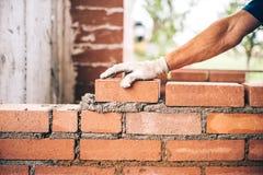 Maurerarbeitskraft, die Ziegelsteine auf Zement beim Errichten von Außenwänden, Industriedetails setzt Stockbild