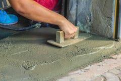 Maurerarbeitskraft-Gebrauchskelle, die flüssigen Beton von glatt gemacht wird oder planiert ist lizenzfreie stockfotografie
