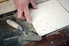 Maurerdachdeckerhand, die eine Fliese auf den Fußboden legt Lizenzfreies Stockbild
